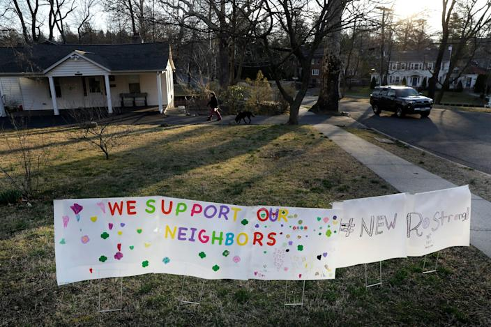 A sign showing support for residents is displayed on a lawn in New Rochelle, N.Y., Wednesday, March 11, 2020. State officials are shuttering several schools and houses of worship for two weeks in the New York City suburb and sending in the National Guard to help with what appears to be the nation's biggest cluster of coronavirus cases, Gov. Andrew Cuomo said Tuesday.