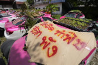 """Workers from two taxi cooperatives assemble miniature gardens on the rooftops of unused taxis parked in Bangkok, Thailand, Thursday, Sept. 16, 2021. Taxi fleets in Thailand are giving new meaning to the term """"rooftop garden,"""" as they utilize the roofs of cabs idled by the coronavirus crisis to serve as small vegetable plots and raise awareness about the plight of out of work drivers. Poster reads """"Due to COVID, life is destroyed."""" (AP Photo/Sakchai Lalit)"""