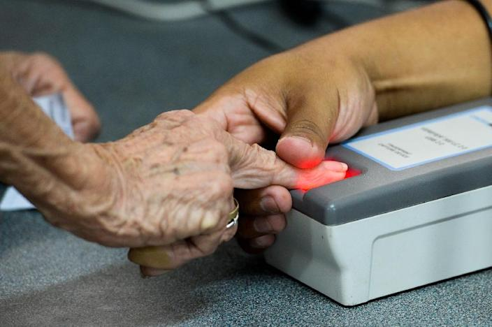 A woman puts a finger on a fingerprint scanner during the authentication procedure of her signature for a recall referendum before the National Electoral Council (CNE) in Caracas, on June 20, 2016 (AFP Photo/Federico Parra)
