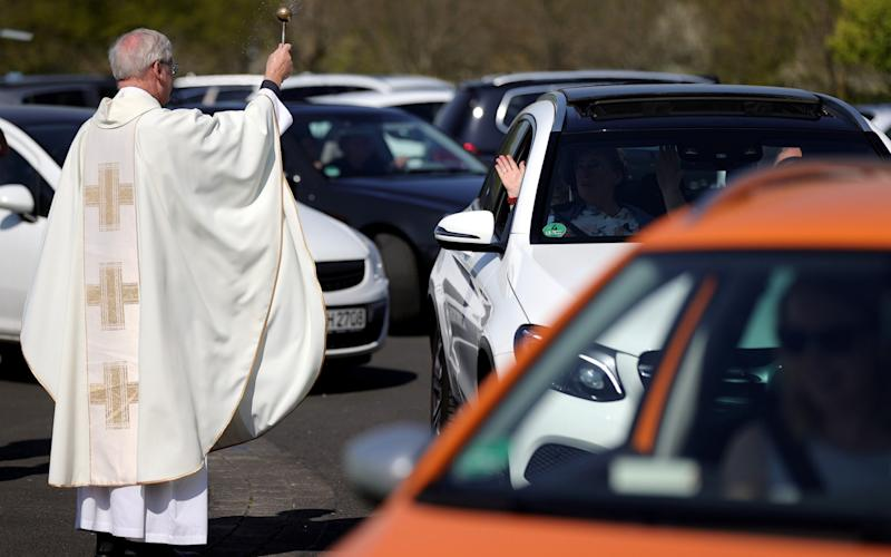 Mandatory Credit: Photo by FRIEDEMANN VOGEL/EPA-EFE/Shutterstock (10610921w) Pastor Frank Heidkamp blesses the vehicle and sprinkles it with holy water after the Catholic Easter service at a drive-in cinema in Duesseldorf, Germany, 12 April 2020. In the new drive-in cinema on the parking lot of exhibition grounds, three church services will be held during the Easter holidays. Churches in Germany have been closed due to the ongoing pandemic of the COVID-19 disease caused by the SARS-CoV-2 coronavirus. Easter Sunday is one of the most important holidays on the Christian calendar, as it marks the resurrection of Jesus Christ. Catholic Easter services drive-in cinema in Duesseldorf, Germany - 12 Apr 2020 - FRIEDEMANN VOGEL/EPA-EFE/Shutterstock