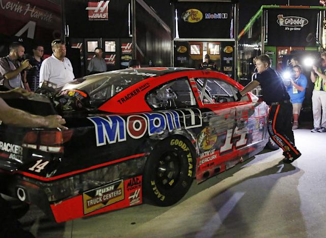 Tony Stewart's car in loaded into the team hauler after hitting the wall in a NASCAR Sprint Cup auto race at Atlanta Motor Speedway Sunday, Aug. 31, 2014, in Hampton, Ga. (AP Photo/Brynn Anderson)