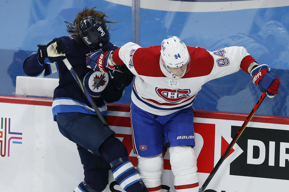 Winnipeg Jets' Sami Niku (8) loses his helmet after a collision with Montreal Canadiens' Corey Perry (94) during the first period of an NHL hockey game Saturday, Feb. 27, 2021, in Winnipeg, Manitoba. (John Woods/The Canadian Press via AP)