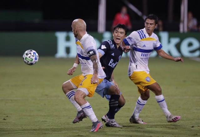 San Jose Earthquakes midfielder Magnus Eriksson, left, Vancouver Whitecaps midfielder Hwang Inbeom, center, and Earthquakes forward Chris Wondolowski vie for the ball during the second half of an MLS soccer match Wednesday, July 15, 2020, in Kissimmee, Fla. (AP Photo/John Raoux)