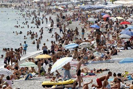 Holidaymakers and tourists sunbathe on the beach on a hot summer day in Nice