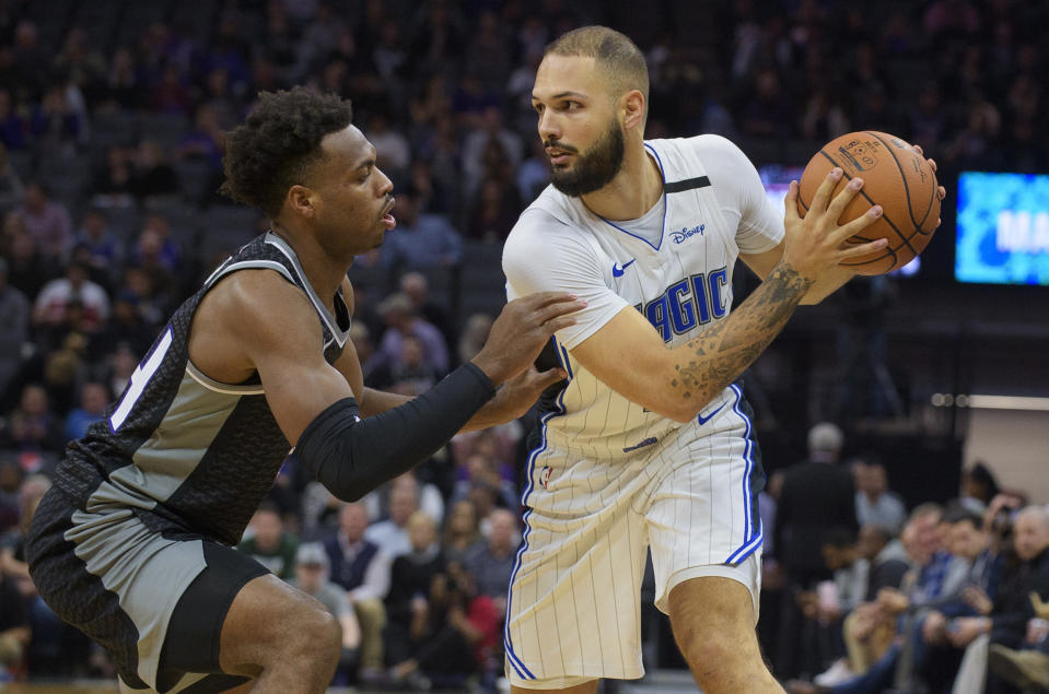 Sacramento Kings guard Buddy Hield (24) defends Orlando Magic guard Evan Fournier (10) during the first quarter of an NBA basketball game in Sacramento, Calif., Monday, Jan. 13, 2020. (AP Photo/Randall Benton)