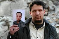 Abu Anas, 26, holds an image of himself when he was 16 years old before artillery shelling caused him to lose his eyesight