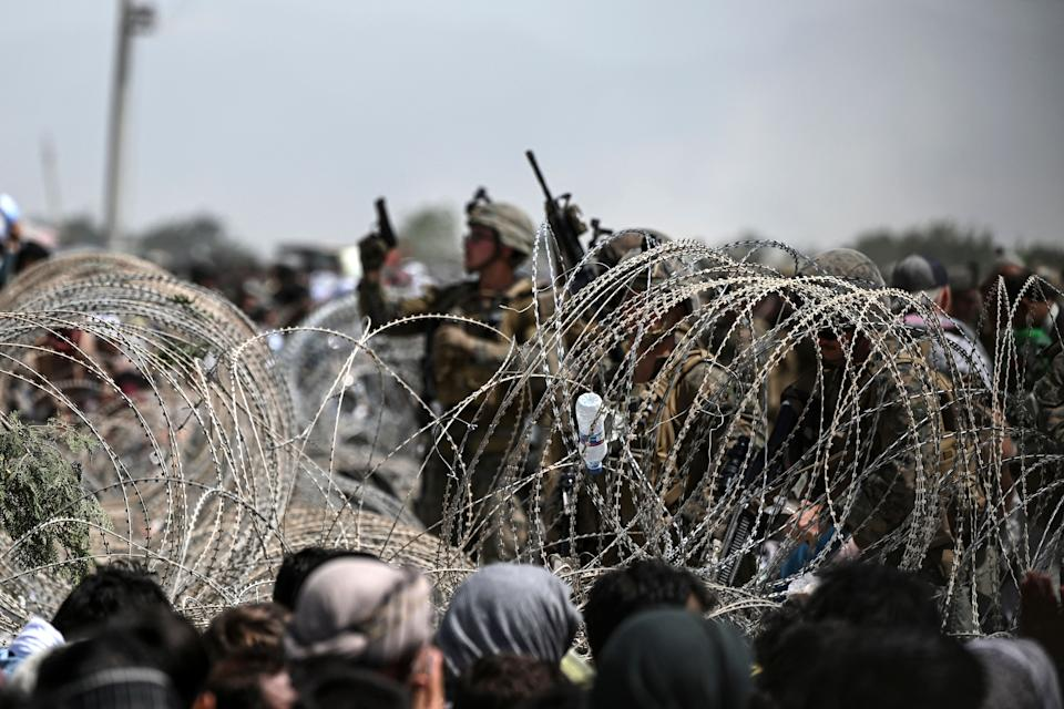 A US soldier shoots in the air with his pistol whiel standing guard behind barbed wire as Afghans sit on a roadside near the military part of the airport in Kabul on August 20, 2021, hoping to flee from the country after the Taliban's military takeover of Afghanistan. (Photo by Wakil KOHSAR / AFP) (Photo by WAKIL KOHSAR/AFP via Getty Images)
