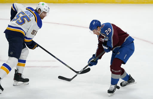Colorado Avalanche center Nathan MacKinnon, right, has the puck slide between his skates after his shot was blocked by St. Louis Blues defenseman Colton Parayko in the first period of an NHL hockey game Friday, Jan. 15, 2021, in Denver. (AP Photo/David Zalubowski)
