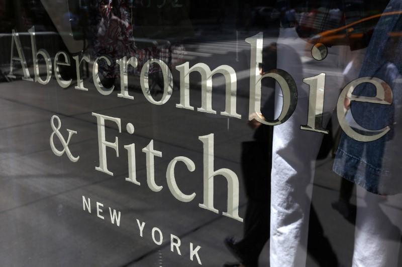 A woman is reflected in a window as she walks past an Abercrombie & Fitch store on 5th Avenue in the Manhattan borough of New York