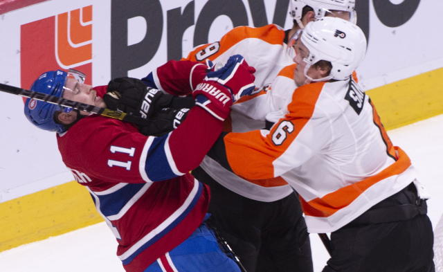 Montreal Canadiens' Brendan Gallagher (11) takes a hit from Philadelphia Flyers defenseman Travis Sanheim during the first period of an NHL hockey game Thursday, Feb. 21, 2019, in Montreal. (Paul Chiasson/The Canadian Press via AP)
