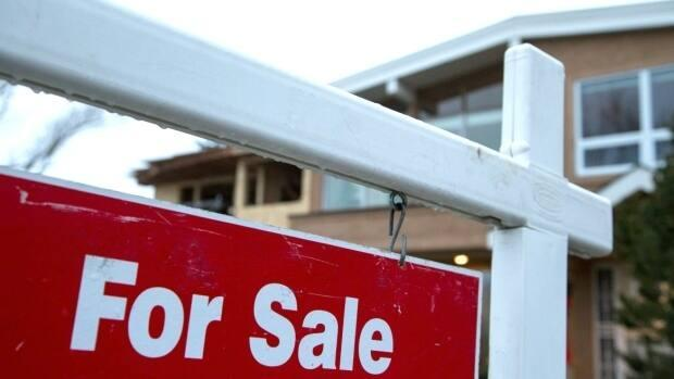 A sign advertises a house for sale in Calgary in this file photo. The pandemic adversely affected major centres across the country, and Calgary was no exception, CMHC says. (Robson Fletcher/CBC - image credit)