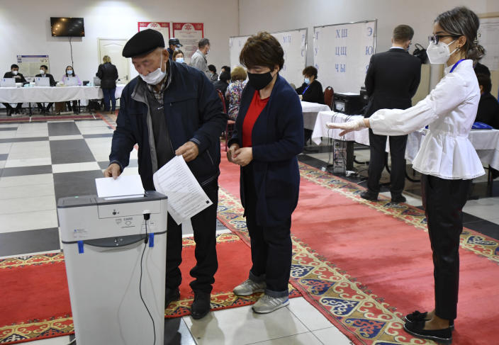 A man casts his ballot at a polling station during the referendum in Bishkek, Kyrgyzstan, Sunday, April 11, 2021. Voters in Kyrgyzstan cast ballots Sunday on whether to approve a new constitution that would substantially increase the president's powers. The Sunday referendum comes three months after Sadyr Zhaparov was elected president, following the ouster of the previous president amid protests, the third time in 15 years that a leader of the Central Asian country had been driven from office in a popular uprising. (AP Photo/Vladimir Voronin)