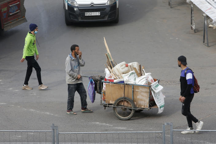 People walk through the streets in Casablanca, Morocco, Tuesday, April 6, 2021. Moroccan authorities have announced the discovery of a new local variant of the coronavirus and extended an overnight curfew as infections rise again. (AP Photo/Abdeljalil Bounhar)