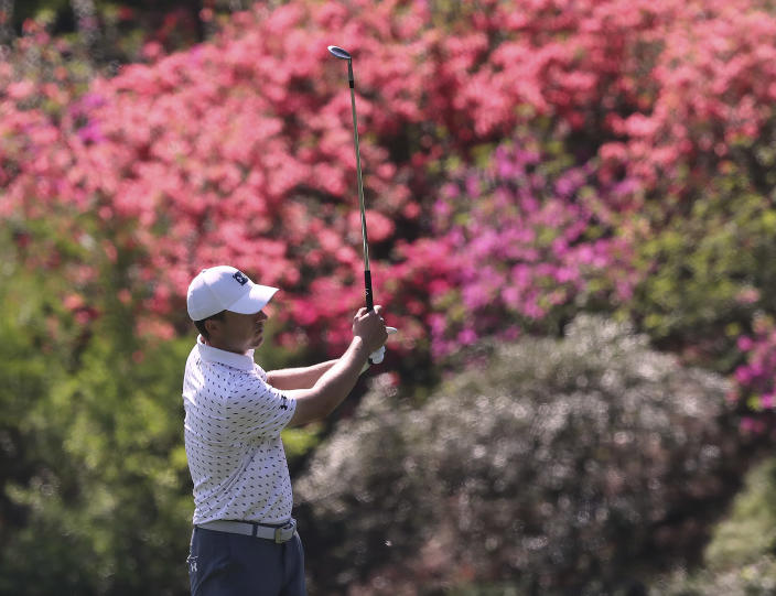 The azaleas are beginning to pop as Jordan Spieth chips to the 13th green during his practice round for the Masters at Augusta National Golf Club on Tuesday, April 6, 2021, in Augusta, Ga. (Curtis Compton/Atlanta Journal-Constitution via AP)