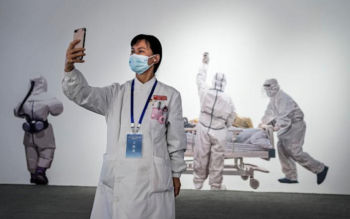 A nurse takes a photo as she visits an exhibition on China's fight against the Covid-19 epidemic at Culture Expo Center in Wuhan - Getty