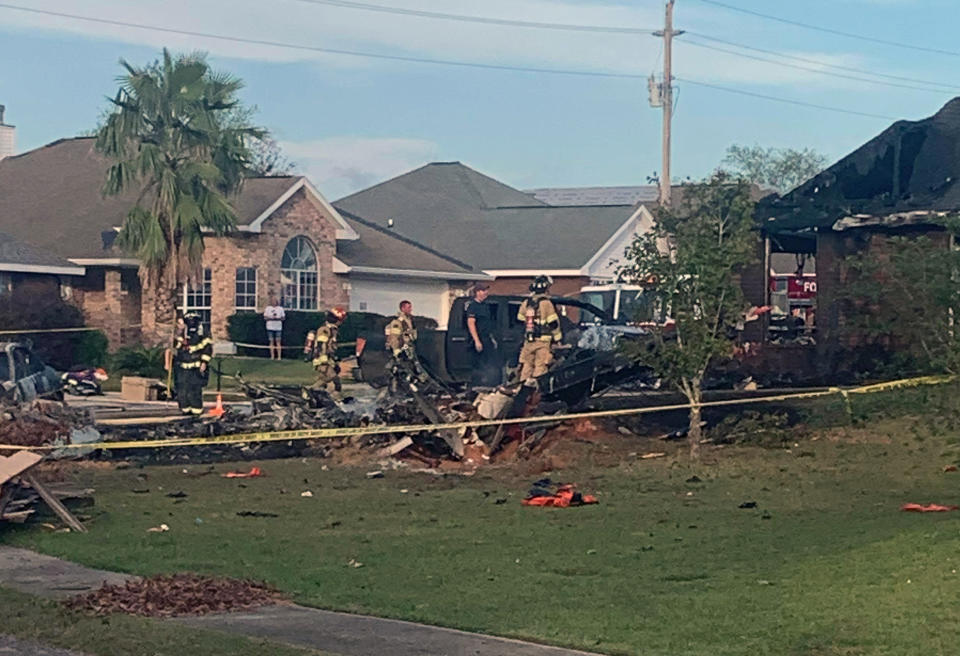Firefighters pictured around a crater on a front lawn.