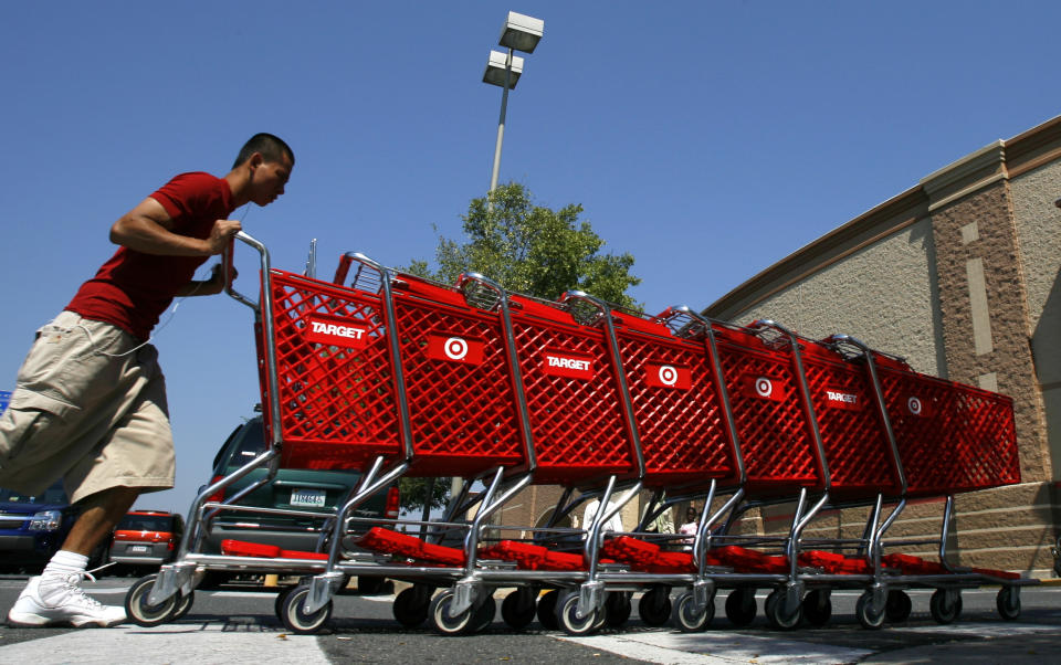 A worker collects shopping carts at a Target store in Falls Church, Virginia August 19, 2008. Target Corp reported a nearly 8 percent drop in quarterly profit on Tuesday as shoppers passed over trendy clothes and home decor in favor of everyday necessities, hurting its margins. REUTERS/Kevin Lamarque   (UNITED STATES)