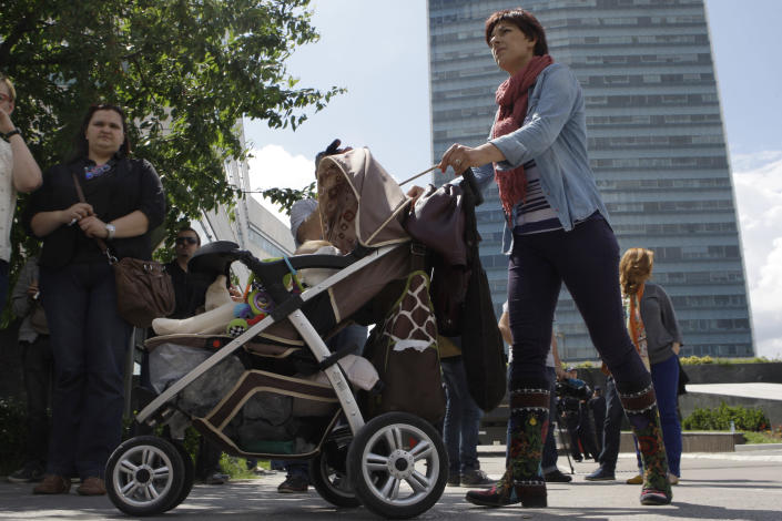 Bosnian woman Selma Zatega , with her baby Luna takes part in a protest in front of the Bosnian parliament building in Sarajevo, on Wednesday, June 5, 2013. Dozens of people are blocking the entrance to Bosnia's Parliament demanding lawmakers to pass a new law on personal identification numbers after the old one came out of force in February, leaving all babies born since then without personal documents. Bosniak, Serb and Croat lawmakers can't agree about the territorial regions that would issue the numbers. The result is depriving newborns the ID numbers needed to get health insurance or a passport. (AP Photo/Amel Emric)
