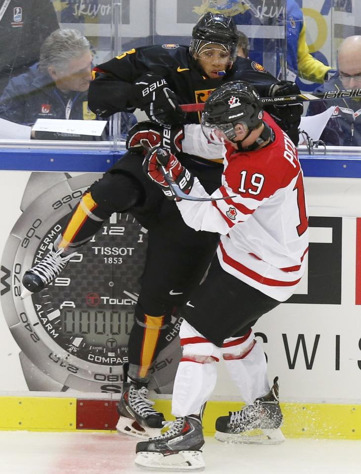 Canada's Nic Petan (R) checks Germany's Lukas Laub during the third period of their IIHF World Junior Championship ice hockey game in Malmo, Sweden, December 26, 2013. REUTERS/Alexander Demianchuk (SWEDEN - Tags: SPORT ICE HOCKEY)
