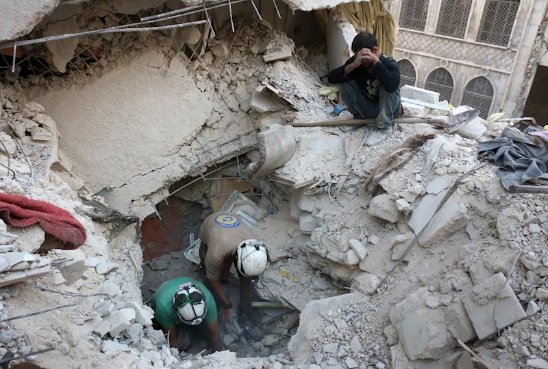Syrian civil defence volunteers search for victims amid the rubble following government air strikes on a rebel-held neighbourhood of Aleppo, on October 4, 2016 (AFP Photo/Thaer Mohammed)