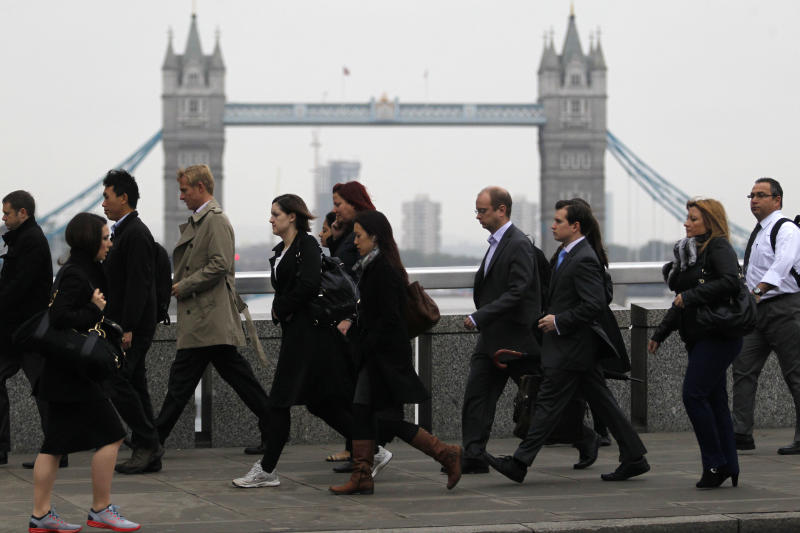 Workers walk across London Bridge on their way to the City of London, Thursday, Oct. 25, 2012. Britain's economy grew by a bigger than expected 1 per cent between July and September, ending a shallow nine-month recession.The figure announced Thursday by the Office for National Statistics beat the market consensus forecast of 0.6 per cent growth. Tower Bridge can be seen in the background. (AP Photo/Sang Tan)