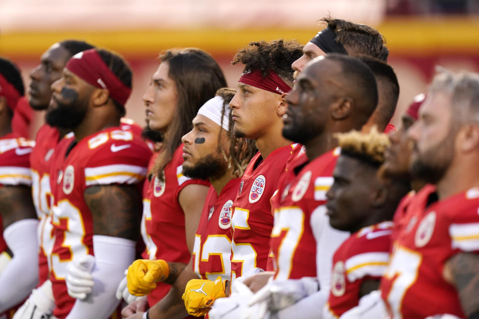 Kansas City Chiefs players stand side-by-side prior to their game.