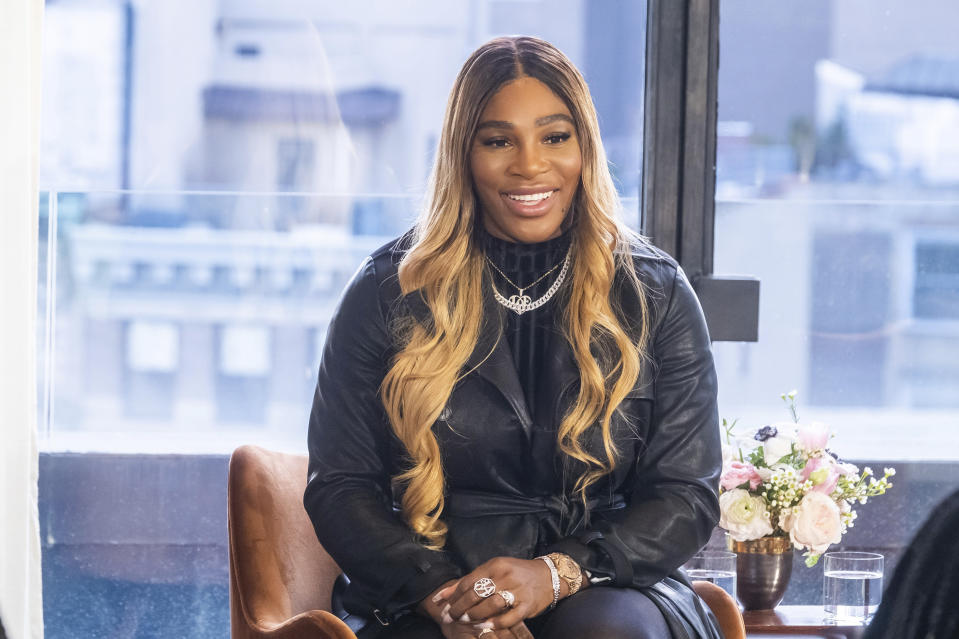 Serena Williams in a black jacket sits in a chair in front of a window in the city.