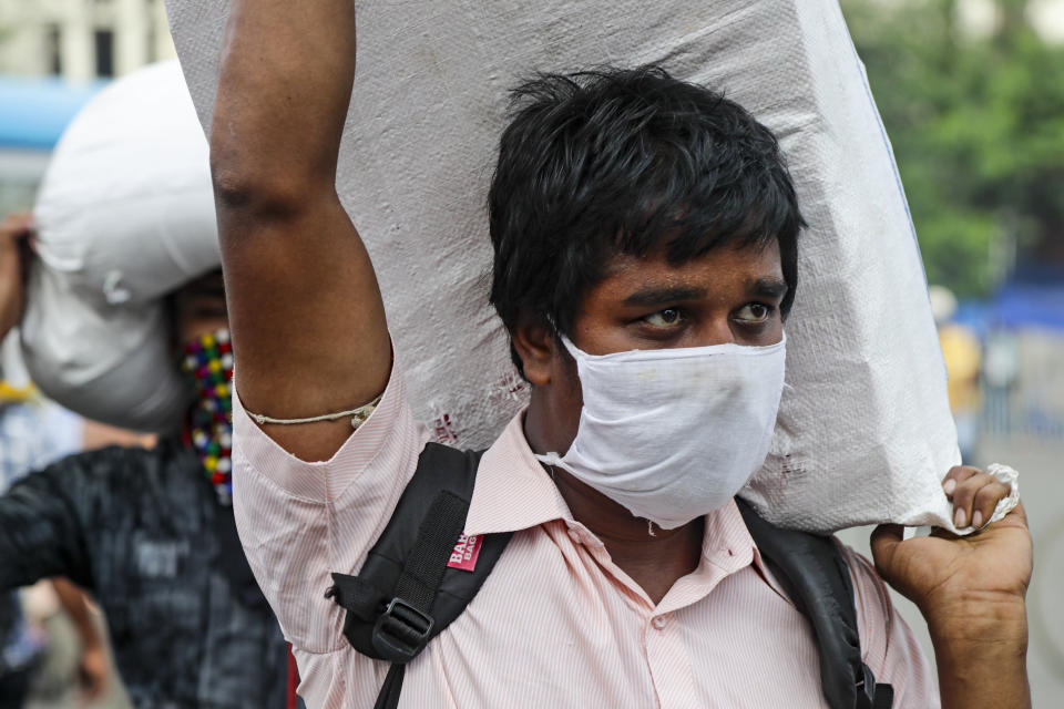 A man wearing a face mask carries a load on his shoulder as he walks to catch a bus in Kolkata, India, Friday, Aug. 14, 2020. India's coronavirus death toll overtook Britain's to become the fourth-highest in the world with another single-day record increase in cases Friday. (AP Photo/Bikas Das)