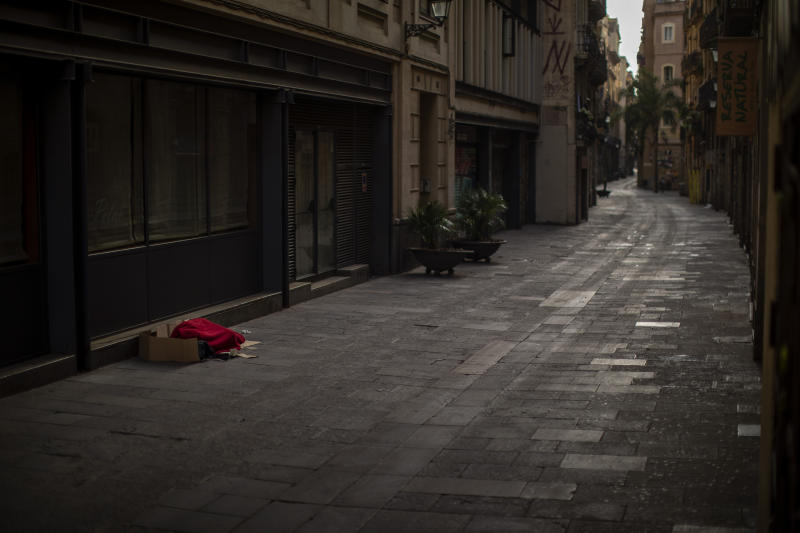 In this Sunday, March 22, 2020 photo, a man covered with a blanket sleeps in an empty street in Barcelona, Spain. In Barcelona sleeping figures with boxes and blankets punctuate the mostly empty city. They are Barcelona's homeless, and there are about 1,000 of them. (AP Photo/Emilio Morenatti)