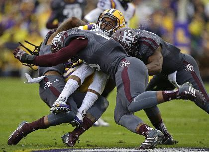 LSU wide receiver Odell Beckham (3) is hit by Texas A&M defensive back Floyd Raven Sr., left, linebacker Donnie Baggs center, and running back Ben Malena, right, while returning a punt in the first half of an NCAA college football game in Baton Rouge, La., Saturday, Nov. 23, 2013. (AP Photo/Gerald Herbert)
