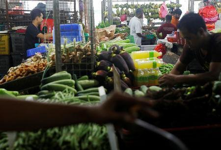 Shopkeepers arrange vegetables at a wet market in Malaysia's southern city of Johor Bahru April 26, 2017. REUTERS/Edgar Su