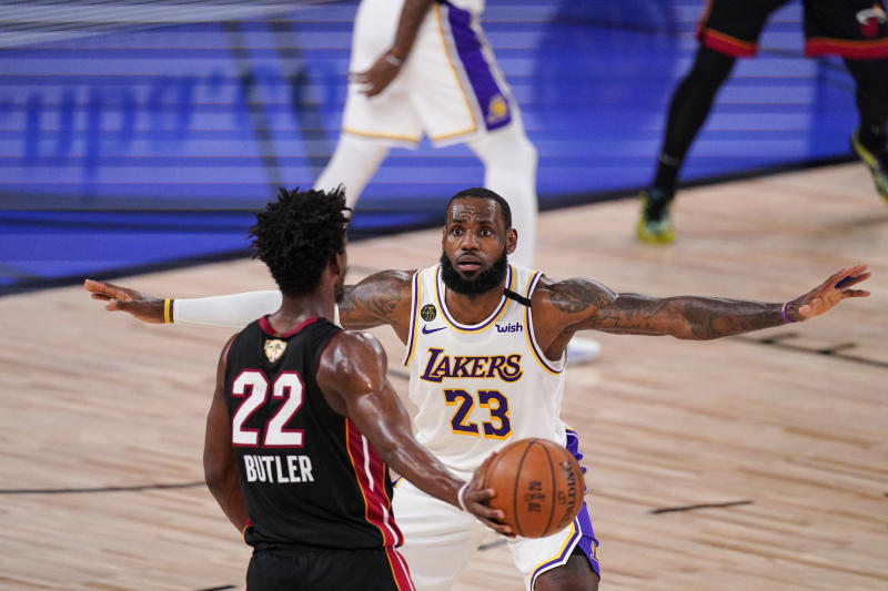 Los Angeles Lakers' LeBron James (23) attempt to block Miami Heat's Jimmy Butler (22) during the first half in Game 3 of basketball's NBA Finals, Sunday, Oct. 4, 2020, in Lake Buena Vista, Fla. (AP Photo/Mark J. Terrill)