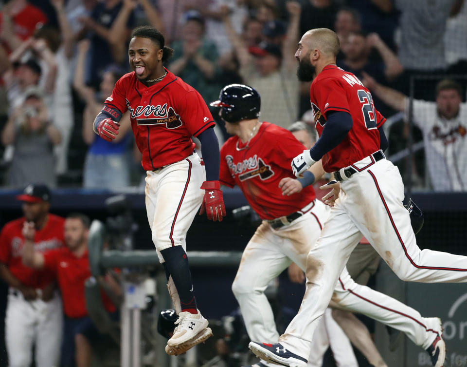 Atlanta Braves' Ozzie Albies, Austin Riley and Nick Markakis, from left, celebrate after the Braves defeated the Philadelphia Phillies 9-8 in a baseball game Friday, June 14, 2019, in Atlanta. (AP Photo/John Bazemore)