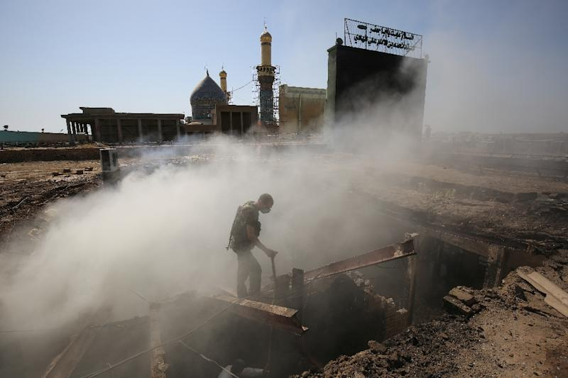 A policeman inspects the scene of a mortar and bombing attack on the Sayyid Mohammed shrine in the Balad area, located 70 kilometres (around 45 miles) north of Baghdad, on July 8, 2016 (AFP Photo/Ahmad al-Rubaye)