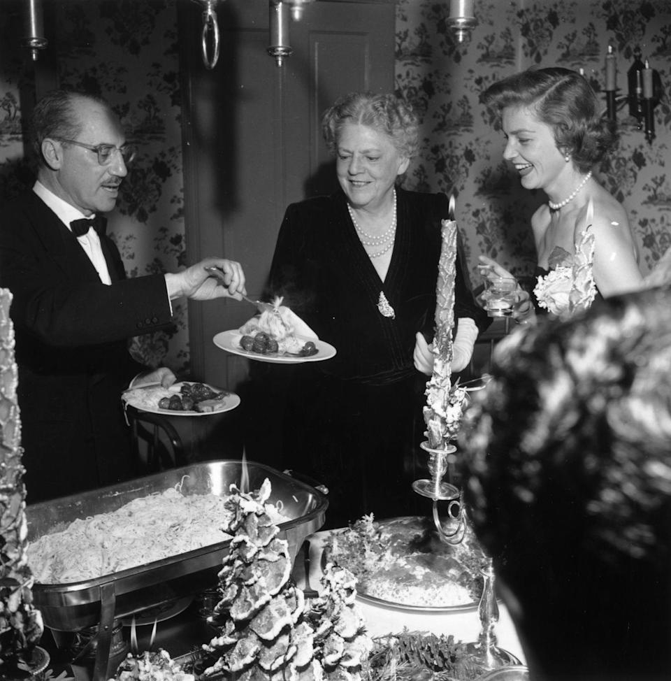 <p>Bacall hosts a family gathering at her Beverly Hills home, which she shared with husband Humphrey Bogart, in 1951.</p>