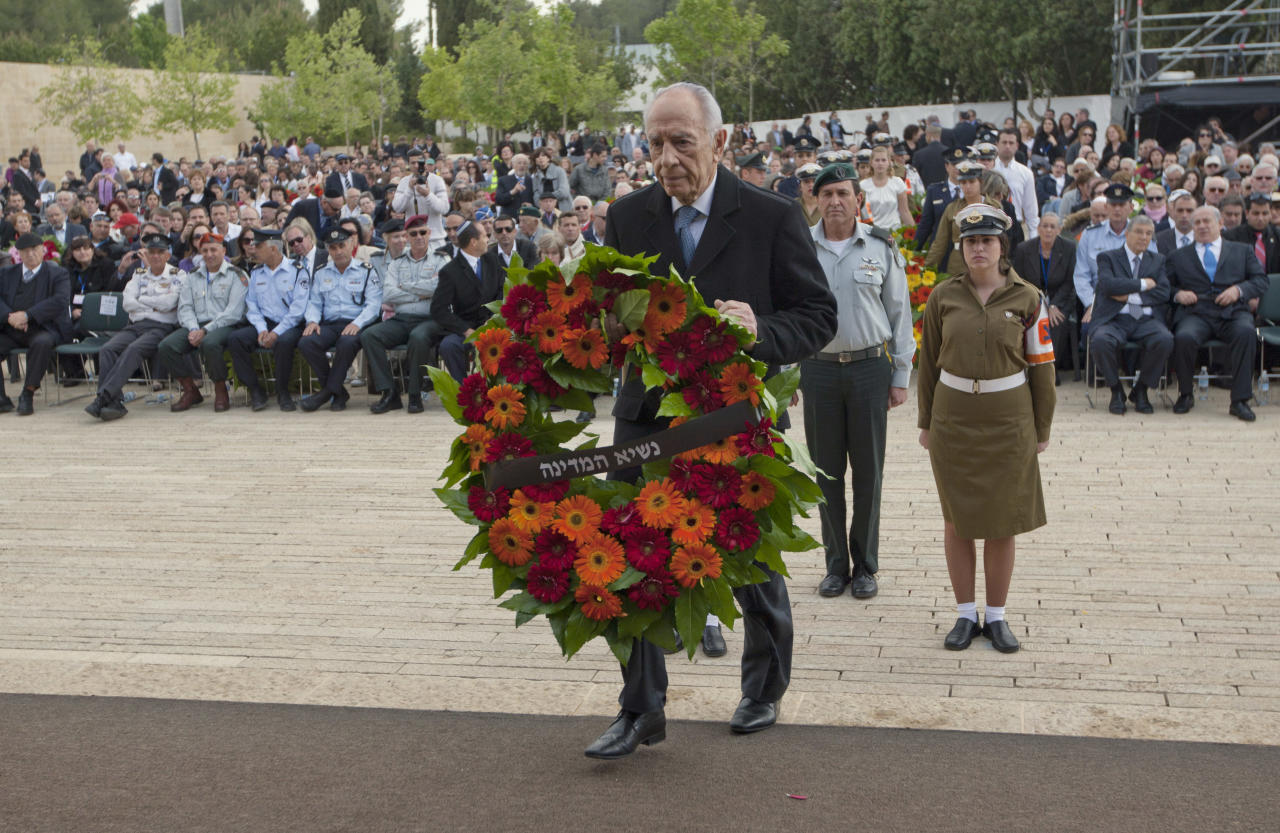 Israel's President Shimon Peres lays a wreath during the annual ceremony in memory of six million Jews who perished in the Nazi holocaust, on Holocaust Remembrance Day at Yad Vashem memorial in Jerusalem, Thursday, April 19, 2012. Israel is marking its annual remembrance day for the six million Jews killed by the Nazis in World War II. (AP Photo/Ariel Schalit, Pool)