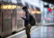A young man wearing a face mask waits for a train in the central station in Frankfurt, Germany, Sunday, March 21, 2021. On Monday, German politics will discuss further measures to avoid the outspread of the coronavirus. (AP Photo/Michael Probst)