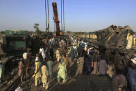Railway workers remove wreckage to clear the track at the site of a train collision in the Ghotki district, southern Pakistan, Tuesday, June 8, 2021. The death toll from a deadly train accident in southern Pakistan jumped to dozens on Tuesday after rescuers pulled a dozen more bodies from crumpled cars of two trains that collided on a dilapidated railway track a day ago, an official said, as rescue work continued even 24 hours after the incident to find any survivors. (AP Photo/Fareed Khan)