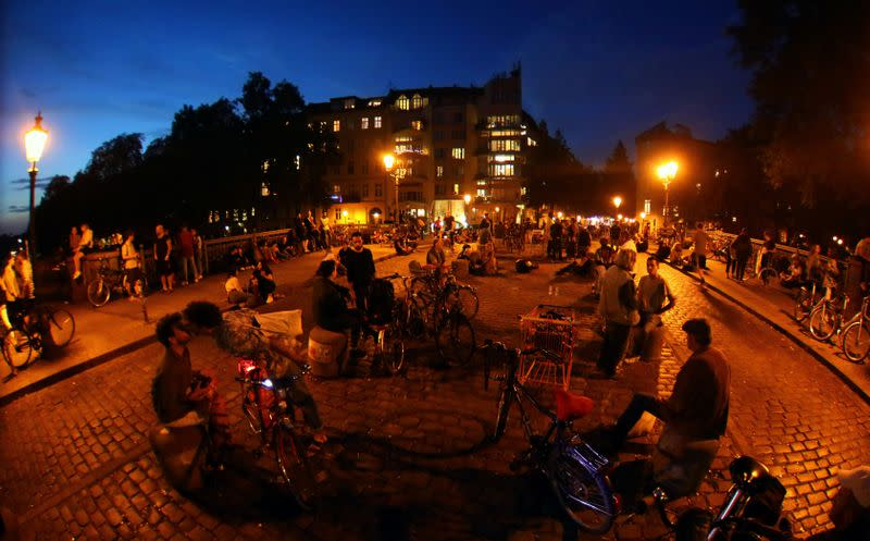 FILE PHOTO: People sit after sunset at the admiral bridge, a popular meeting point for tourists and residents, amid the coronavirus disease (COVID-19) outbreak, in Berlin