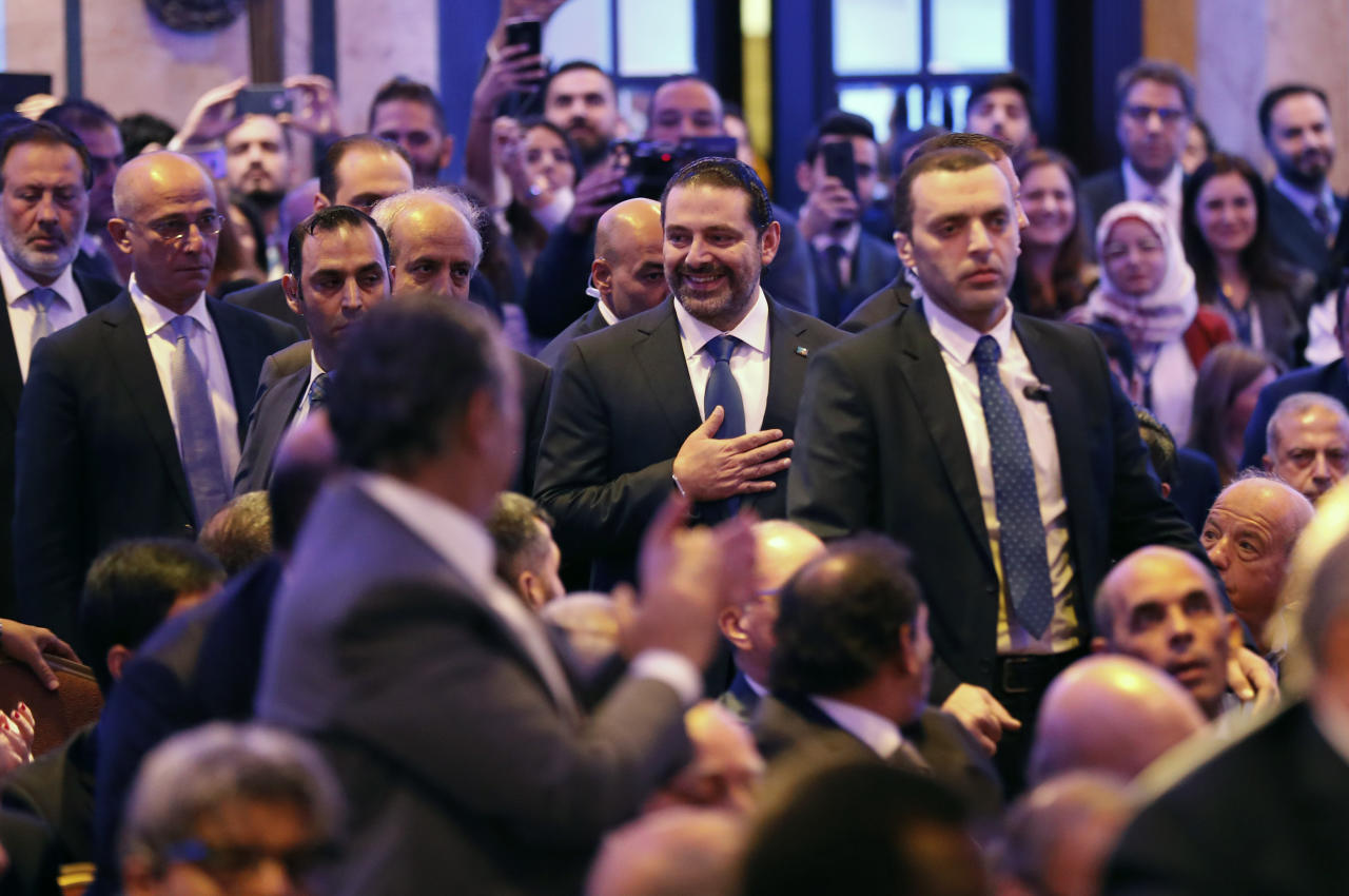 Lebanese Prime Minister Saad Hariri, center, greets the audience on his arrival to a regional banking conference, in Beirut, Lebanon, Thursday, Nov. 23, 2017. Hariri told the conference that the country's stability is his primary concern. The remarks, a day after Hariri suspended his resignation, sought to assure the Hariri's government would keep up the effort to have Lebanon remain a top Mideast destination for finance. (AP Photo/Hussein Malla)