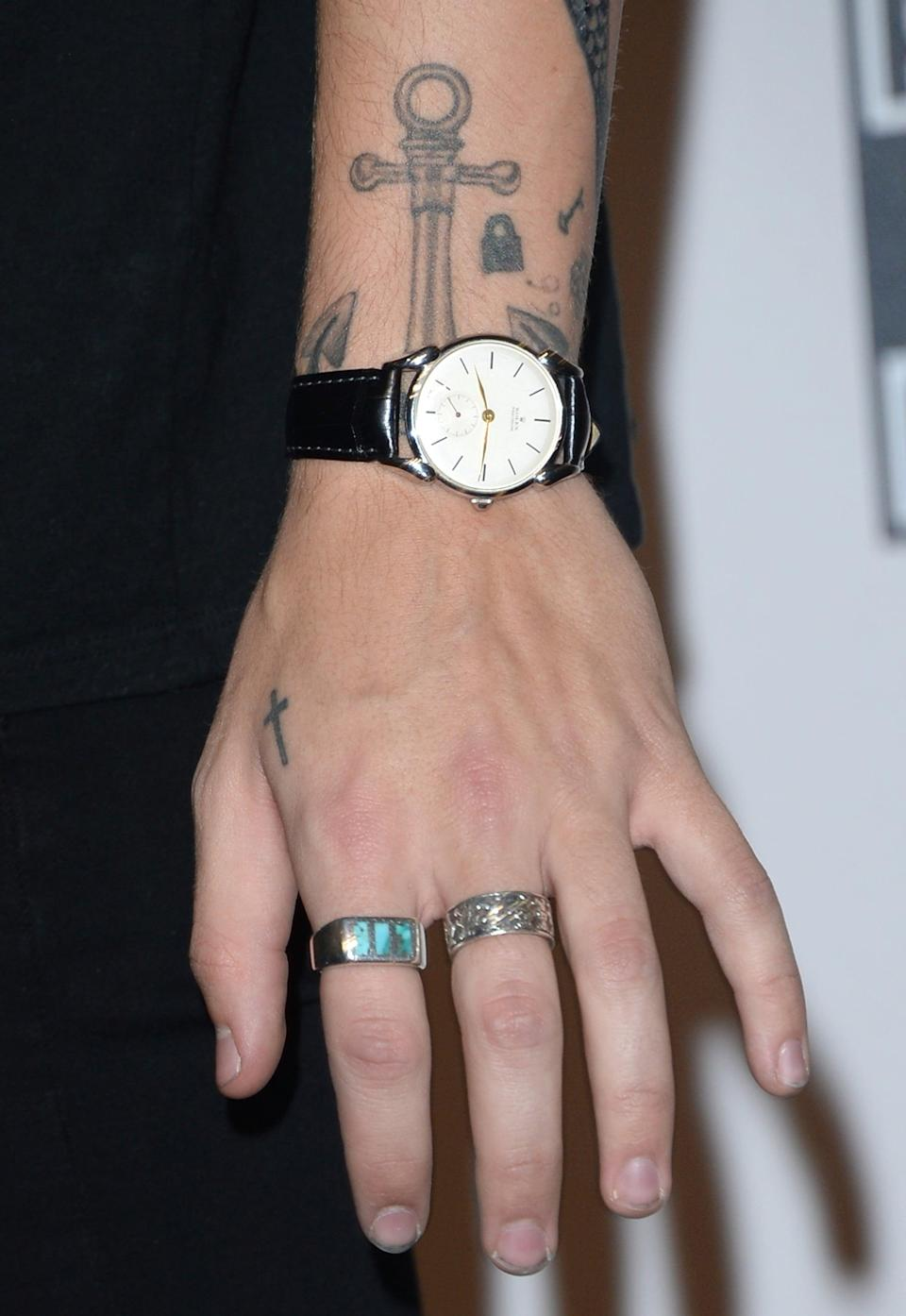 """<p>Styles has a few scattered tattoos on his left wrist, including a padlock that was <a href=""""https://www.gq-magazine.co.uk/grooming/article/harry-styles-tattoos"""" class=""""link rapid-noclick-resp"""" rel=""""nofollow noopener"""" target=""""_blank"""" data-ylk=""""slk:inked by Ed Sheeran"""">inked by Ed Sheeran</a>, as well as a small Aquarius symbol, which is his star sign, and """"99p.""""</p>"""