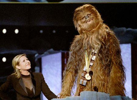 """FILE PHOTO: Chewbacca, the eight-foot tall, 200 year-old """"wookie"""" character from """"Star Wars,"""" gives his acceptance speech in his own tongue upon receiving the MTV Movie Awards Lifetime Achievement from Carrie Fisher (L), who played Princess Leia Organa in the same movie, June 7, 1997. REUTERS/File Photo"""