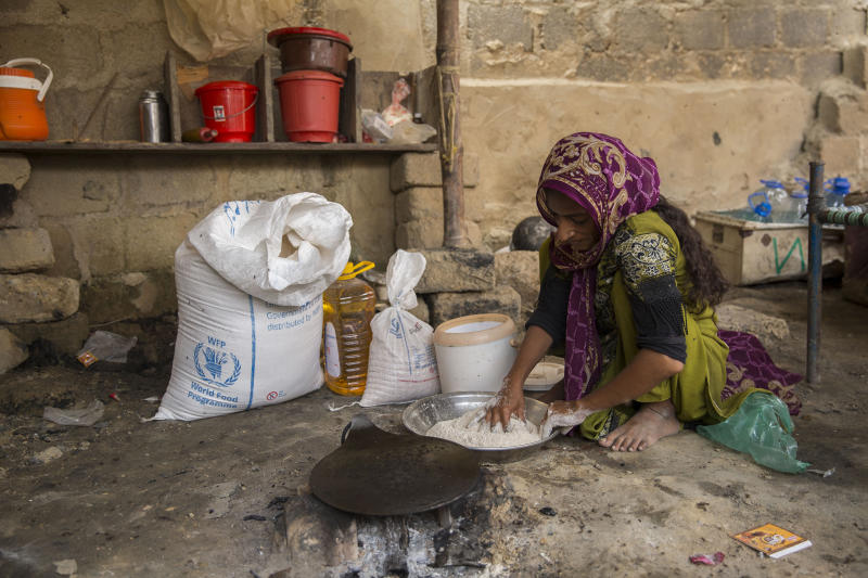 Salam Nasrullah mixes wheat flour that she received from the WFP as part of a ration package distributed to affected familiesSaiyna Bashir/Arete/WFP