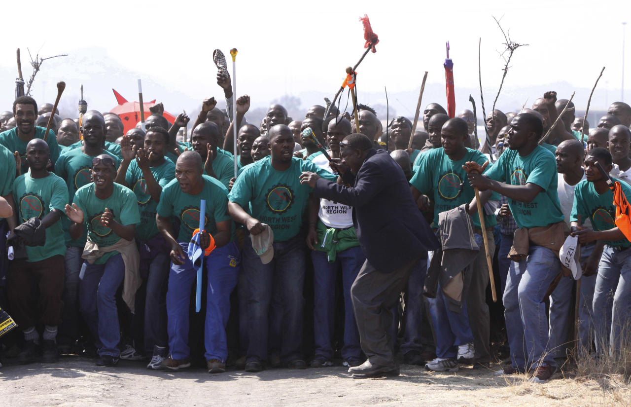 Mourners make their way to a memorial service at the Lonmin Platinum Mine near Rustenburg, South Africa, Thursday, Aug. 23, 2012 after police shot and killed 34 striking miners and wounded 78 last week. Demands for higher wages spread to at least two other mines, raising fears of further protests at more South African mines that provide most of the world's platinum. (AP Photo/Denis Farrell)