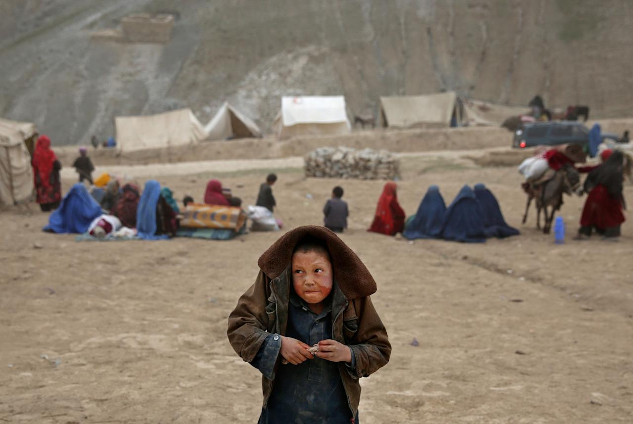 In this Sunday, May 4, 2014 photo, an Afghan child protects himself from the rain, near the site of Friday's landslide that buried Abi-Barik village in Badakhshan province, northeastern Afghanistan. Stranded and with no homes, many of the families have struggled to get aid. Some have gone to nearby villages to stay with relatives or friends, while others have slept in tents provided by aid groups. The unlucky ones have slept outside. (AP Photo/Massoud Hossaini)