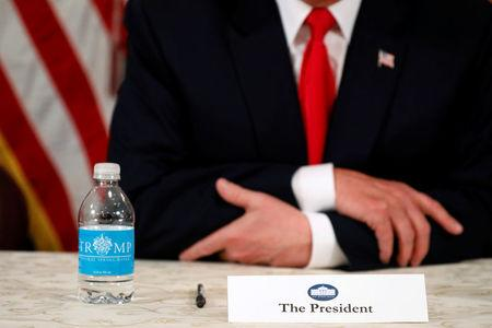 U.S. President Donald Trump, with a bottle of Trump-branded water, speaks to reporters after a security briefing at his golf estate in Bedminster, New Jersey U.S. August 10, 2017.  REUTERS/Jonathan Ernst