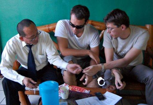 Swedish nationals Bo Stefan Sederholm (centre) and Emil Andreas Solemo talk to their Philippine lawyer prior to their sentencing at a court in Mindanao on May 10. The two Swedes were jailed for life in the Philippines for human trafficking after they were found running a cybersex den in which nude women performed for Internet clients