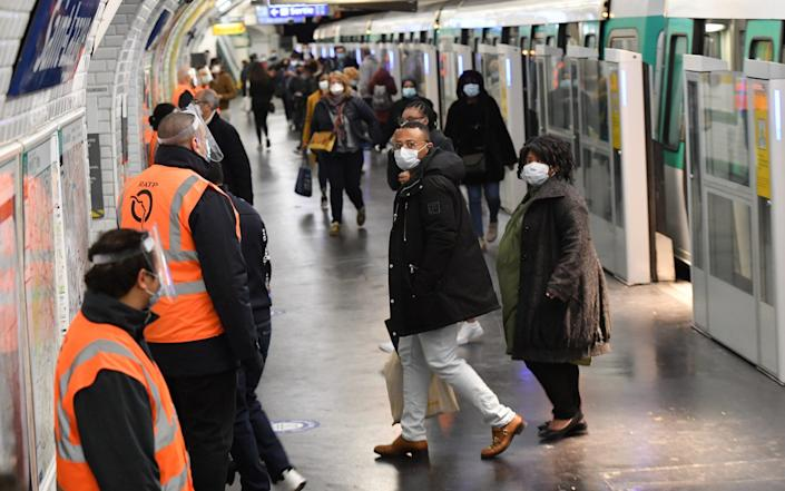 Paris public transport workers in protective face gear watch passengers as they arrive at Saint-Lazare - Stephane Cardinal/ Corbis News
