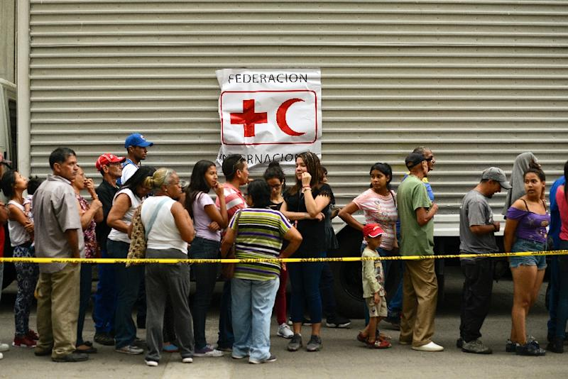 People queue to receive water drums and water purification tablets from the Red Cross in Caracas, Venezuela, on April 16, 2019, after the first shipment of Red Cross humanitarian aid arrived by plane from Panama (AFP Photo/Matias Delacroix)