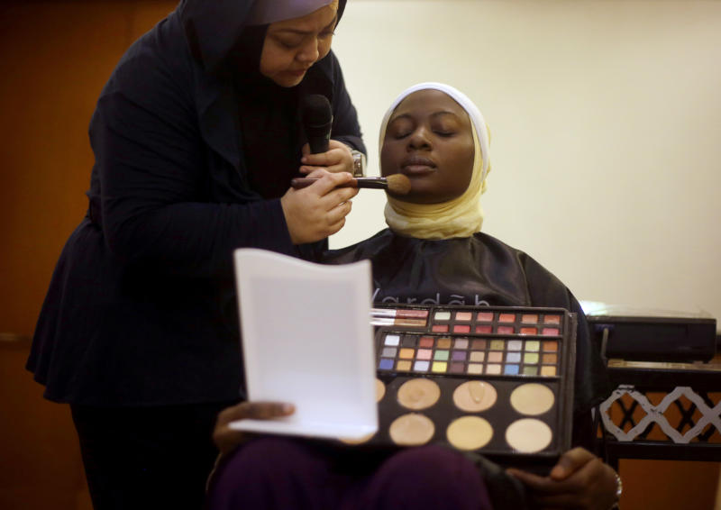In this Monday, Sept. 16, 2013 photo, Obabiyi Aishah Ajibola of Nigeria has her make up applied during a beauty class part of the 3rd Annual Award of World Muslimah, a competition billed as the Islamic alternative to Miss World pageant, in Jakarta, Indonesia. Beauty queens and backstage drama may seem inevitable, but at this year's Miss World competition, something more serious than hair-pulling and name-calling has come from host country Indonesia: Muslim hardliners have threatened to hijack the competition despite major concessions from the government and organizers. (AP Photo/Dita Alangkara)